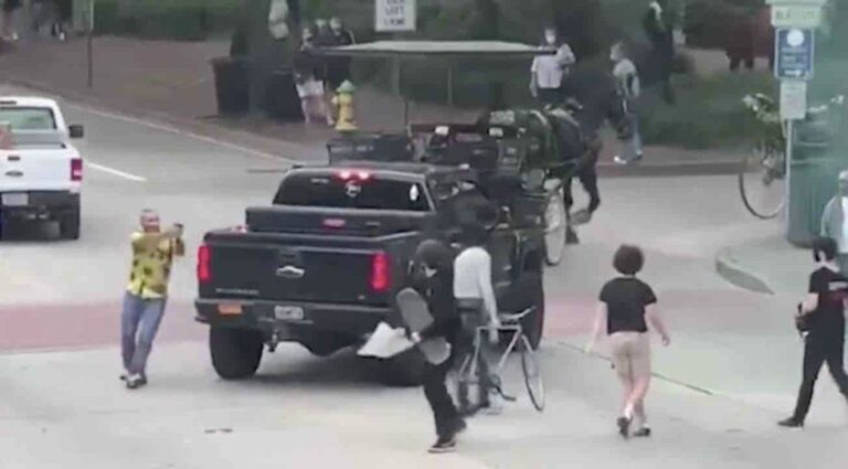 Motorist pulls gun on Black Lives Matter protesters attacking his truck. They were blocking road, and he tossed smoke grenade at them, cops say.