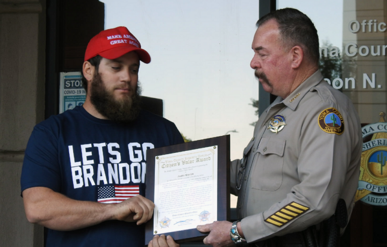 Marine Corps veteran who stopped armed robbery accepts valor award wearing 'Let's Go Brandon' shirt and a MAGA hat